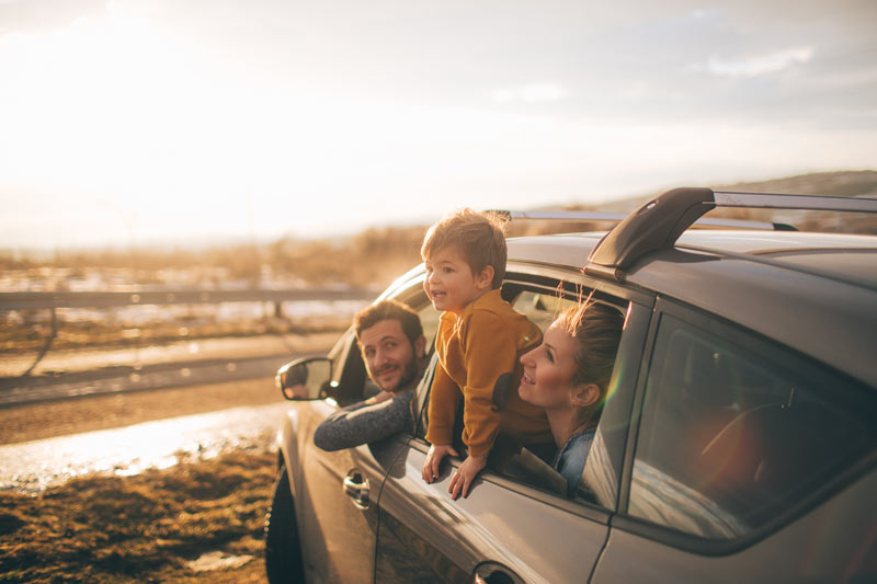 A family in their car overlooking a beach