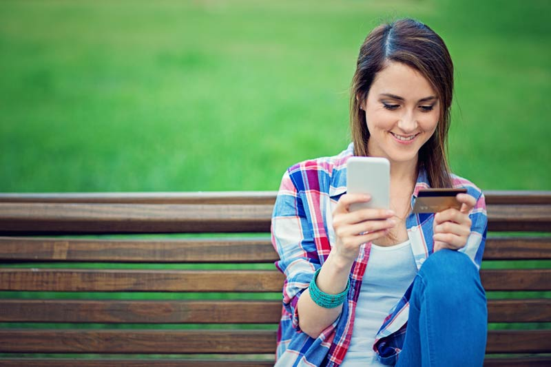 A girl in a plaid shirt looking at her smart phone on a bench